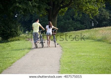 A young couple pushing bicycles