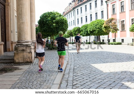 A young couple running along the historical side of the city of Wroclaw