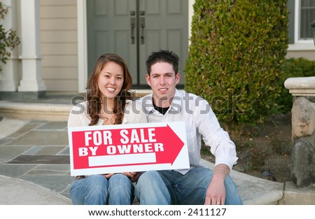 A young couple selling their home holding a sale sign