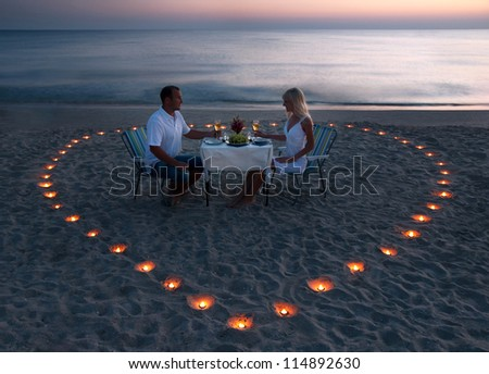 A young couple share a romantic dinner with candles heart on the sea sand beach - stock photo