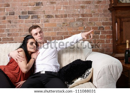 A young couple sitting close on the sofa
