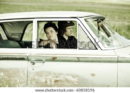 A young couple sitting in a old car./Young Couple in Old Car