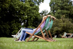 A young couple sitting on deckchairs in St James Park