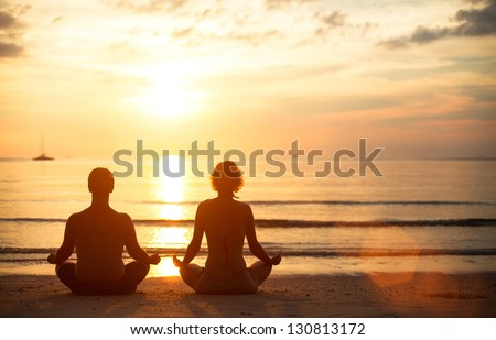A young couple sitting on the beach of the sea in the lotus position at sunset, yoga practice