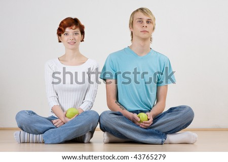 A young couple sitting on the floor with legs crossed in a Yoga position.