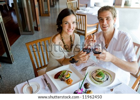 A young couple sitting together in a restaurant holding hands