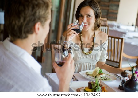 A young couple sitting together in a sophisticated restaurant