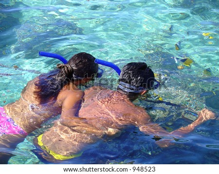 A young couple snorkeling in the clear blue tropical water.