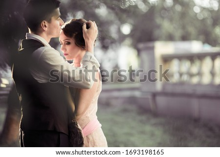 A young couple stands against a backdrop of large trees and a fence. A man adjusts the hair on a woman