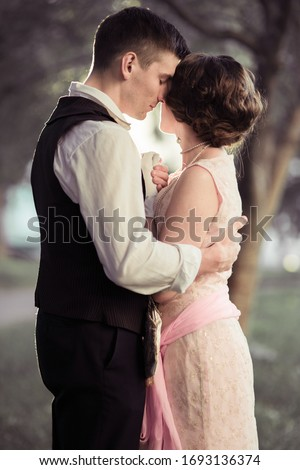 A young couple stands against a background of large trees. The man looks at the woman and hugs her. Historical reconstruction Photo stock ©