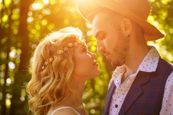 A young couple stare into each other's eyes, in the rays of the setting sun on a summer day. close-up