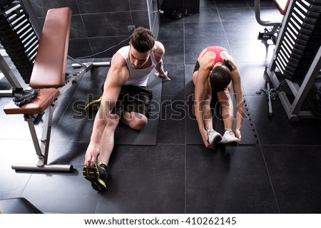 A young couple stretching in the gym