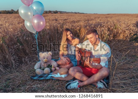 A young couple summer sitting wheat field. Romantic evening, outdoor recreation. The concept of love music guitar. The concept of gift and holiday. Emotions are pleasure pleasure and tenderness.