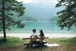 A young couple - the bride and groom are sitting on a bench on the background of the lake and looking at each other.