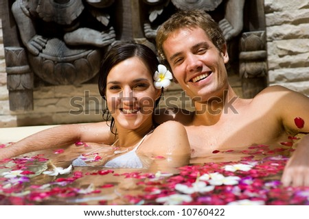 A young couple together in a bath with petals and flowers at a tropical spa