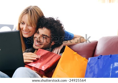 a young couple  using credit card to purchase over the internet, happiness and amazement