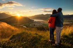 A young couple viewing sunset from the top of a mountain. The beautiful sun produces a warm orange glow to the entire image. Queenstown, New Zealand is a romantic getaway for lovers.