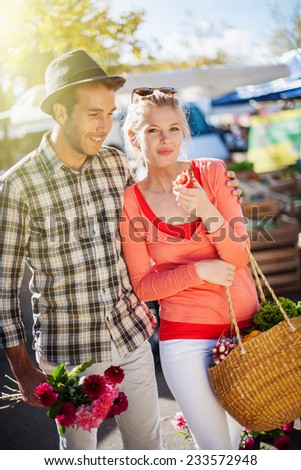 a young couple walking on a market on a sunny morning, the young woman carries a basket with fruit and vegetables
