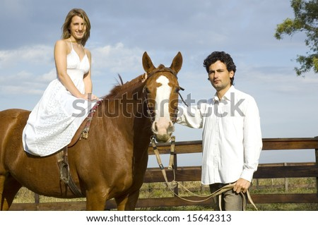 A young couple with their horse - the woman riding and the man leading