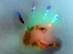 A young cute girl and her beautiful eyes behind a frosty car glass window during a winter time. unique, special  and inventive child, creativity in the childhood, green eyes, hello and bye hand,finger