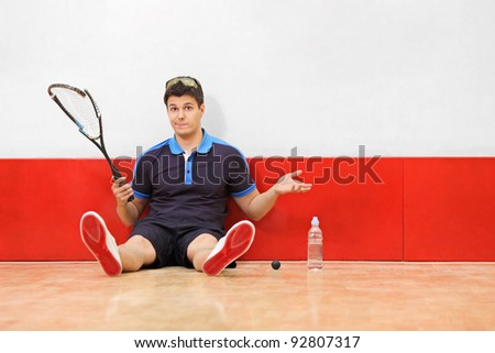 A young disappointed squash player holding a broken racket in a squash court