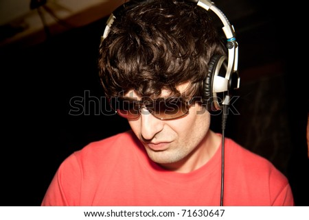 A young DJ  is listening to music on his headphones! Isolated blue background