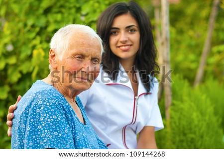 A young doctor / nurse standing next to an elderly sick woman.