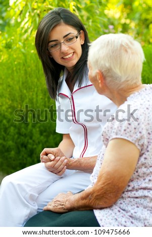 A young doctor / nurse visiting an elderly sick woman and chatting with her outdoors.