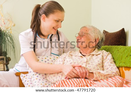 A young doctor / nurse visiting an elderly sick woman holding her hands with caring attitude.