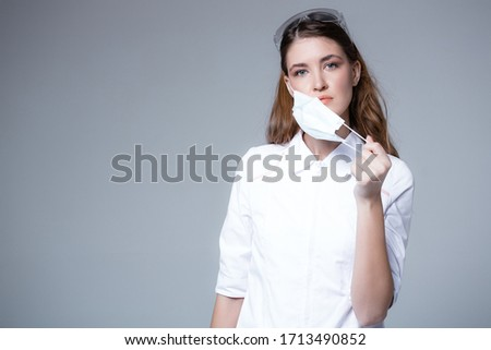 A young doctor takes off a disposable medical mask. Lack of masks and the risk of getting sick without face protection