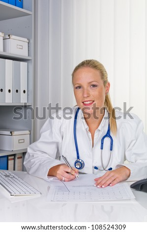 a young doctor with stethoscope in her doctor's office.