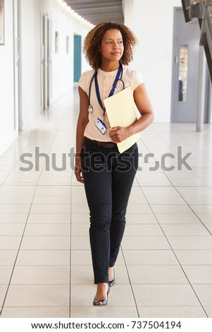 A young doctor with stethoscope, walking in modern lobby