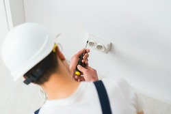 A young electrician installing an electrical socket in a new house.