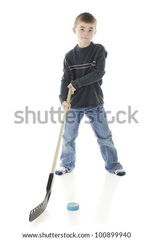 A young elementary boy posing with his hockey stick and puck.  On a white background. - stock photo