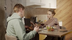 A young emancipated businesswoman does not pay attention to her husband, who prepared a festive dinner. She works remotely on her laptop and makes work calls on her smartphone.