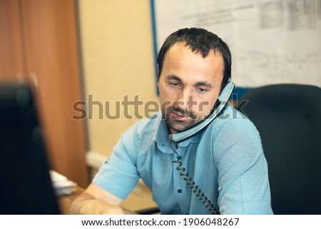 A young employee sits in a chair at a desk in the office and talks on a wired phone. This is a man of Caucasian appearance in a real working environment. The engineer solves production issues. Photo stock ©