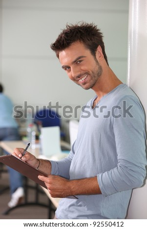 A young employee writing on a notepad and looking at us.