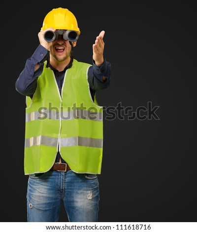 A Young Engineer Looking Through Binoculars On Black Background