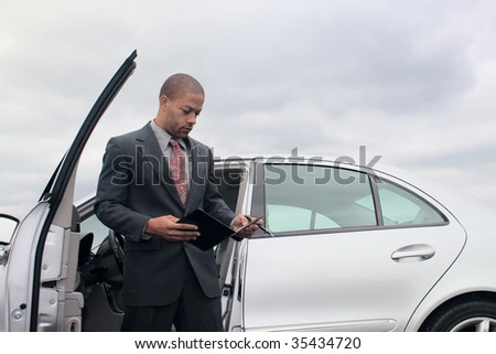 A young ethnic businessman consults his notes while standing next to his car.