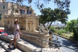 a young european girl in a hat walks through the capital of Malta Valletta