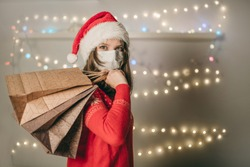 A young European woman in a white medical mask and Christmas red hat walks in the store with gift packages behind her back and bokeh lights, garlands, decoration. Shopping girl, quarantine coronavirus
