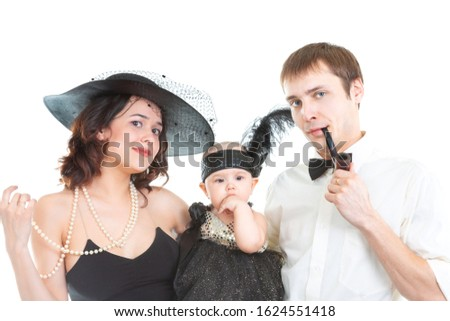 A young family, a young lady, a mother with a baby in her arms in a black retro dress and hat, and a gentleman with tobacco pipe and in a bow tie are photographed in a photo studio