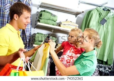 A young family choosing clothing in the shop