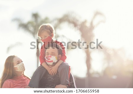 A young family couple and their son walking wearing cloth face masks. Many countries recommend citizens cover their faces during the world coronavirus covid-19 pandemic.