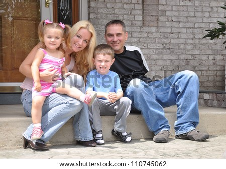 A young family is sitting in front of a home smiling and posing. There is a mother, daughter, father and son. Use it for a love or real estate concept.
