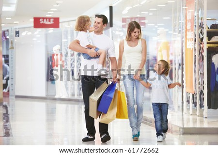 A young family of four with children in the store