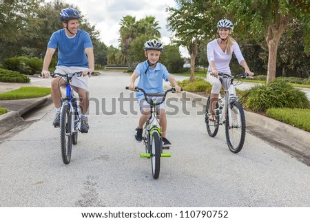A young family of man and woman parents and one boy child, cycling together.