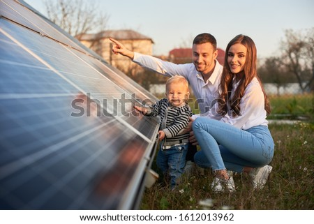 A young family of three is crouching near a photovoltaic solar panel, smiling and looking at the camera, concept of bright future Photo stock ©