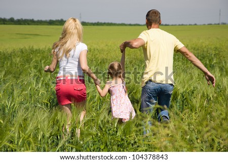 A young family running across the field