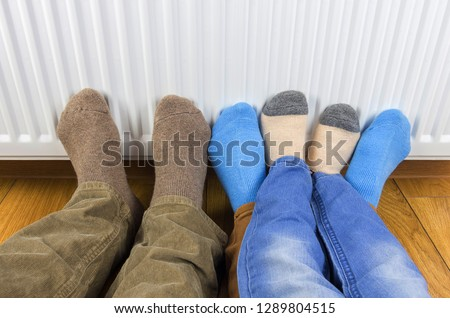 A young family's feet in a pair of warm wool socks warming in front of a heater at home in winter. #1289804515